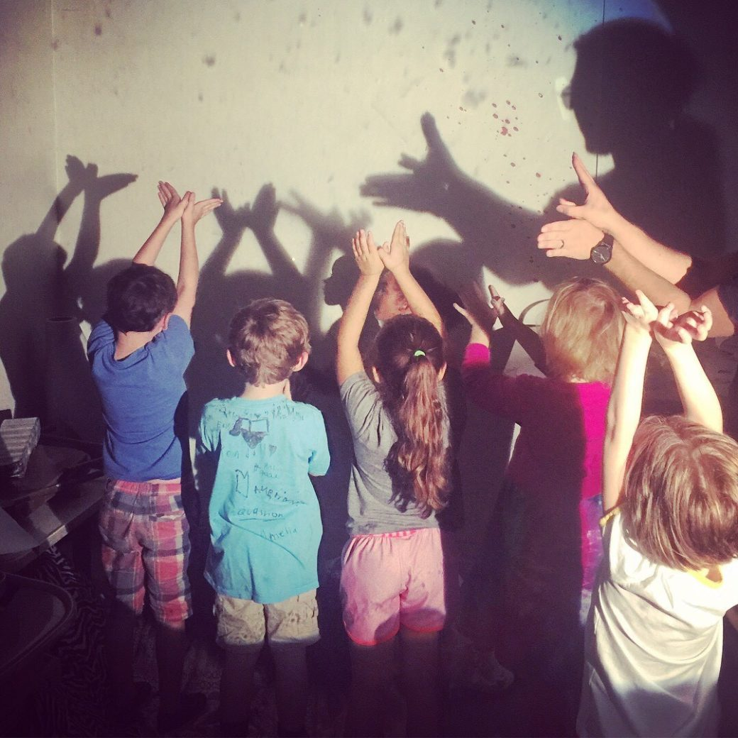 Children making shadow puppets against the wall