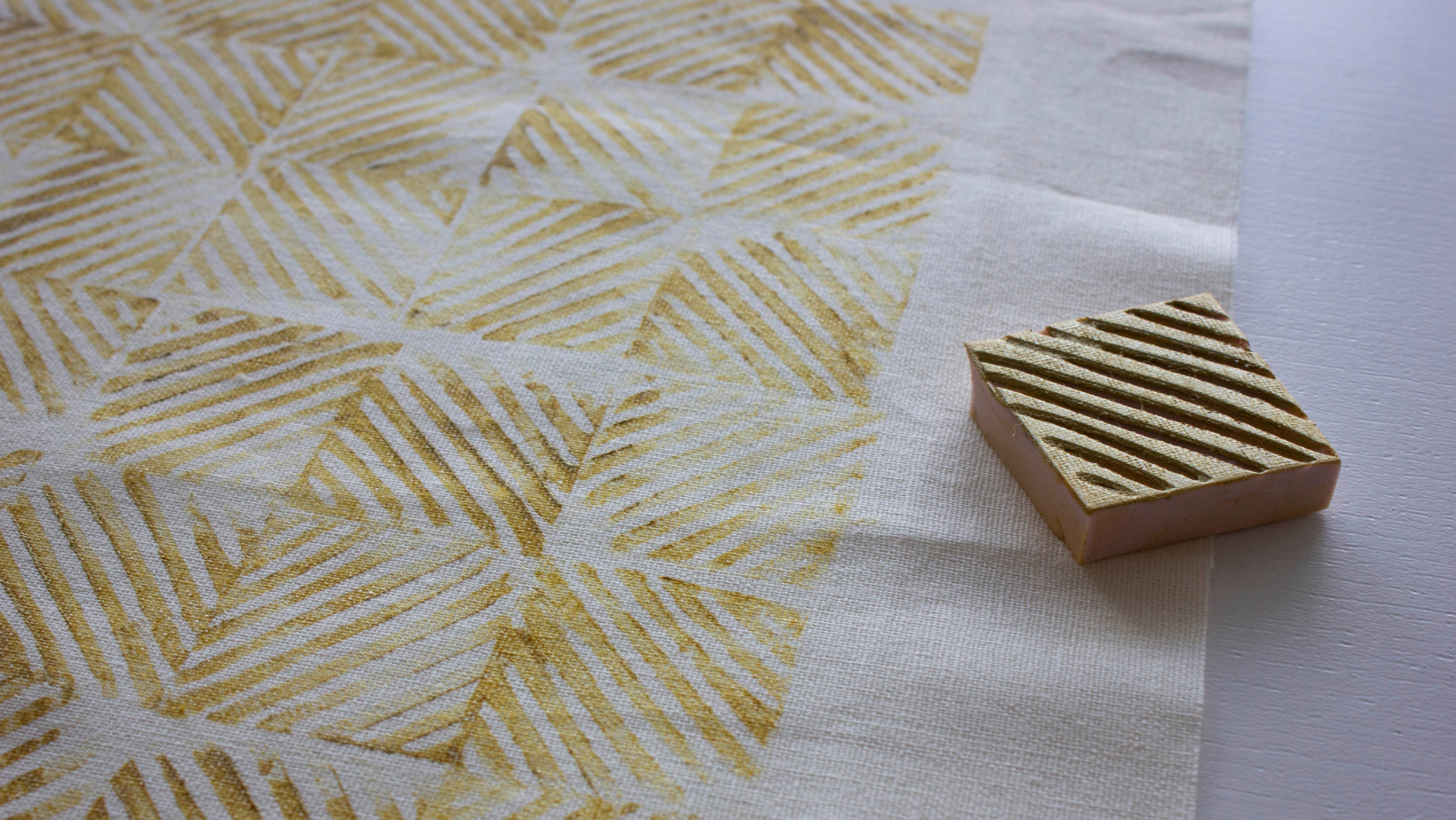 A rubber stamp on a white fabric with a hand printed pattern in yellow ink