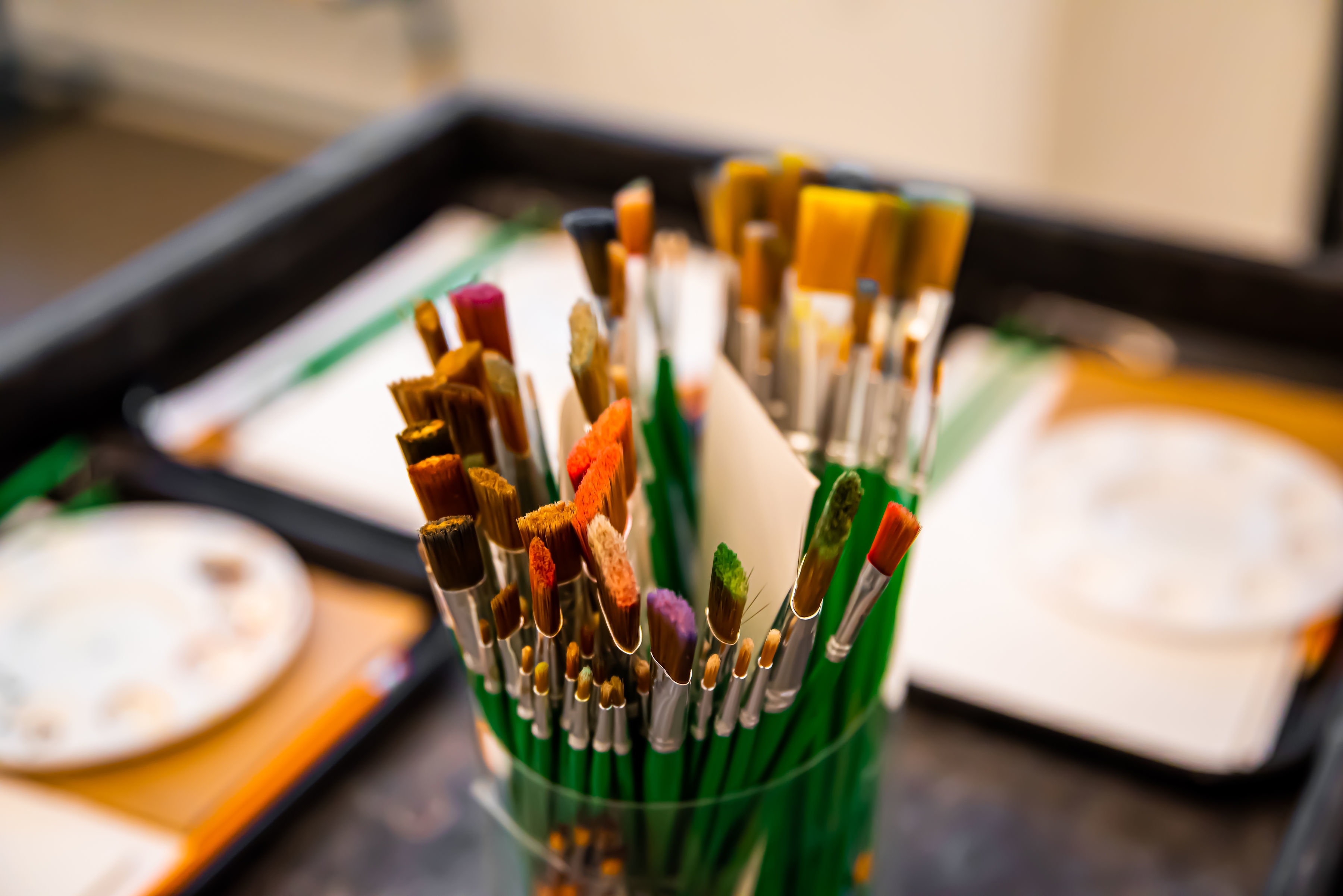A set of paintbrushes in a cup with palettes out of focus in background