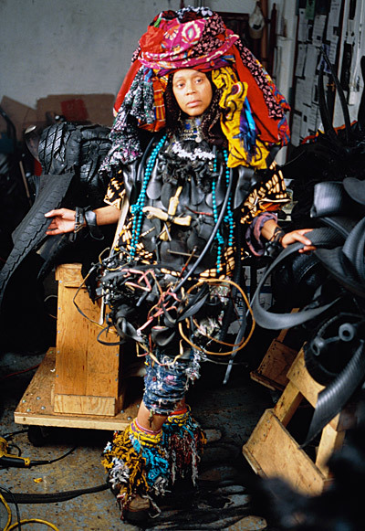 A person wears an elaborate outfit and headdress