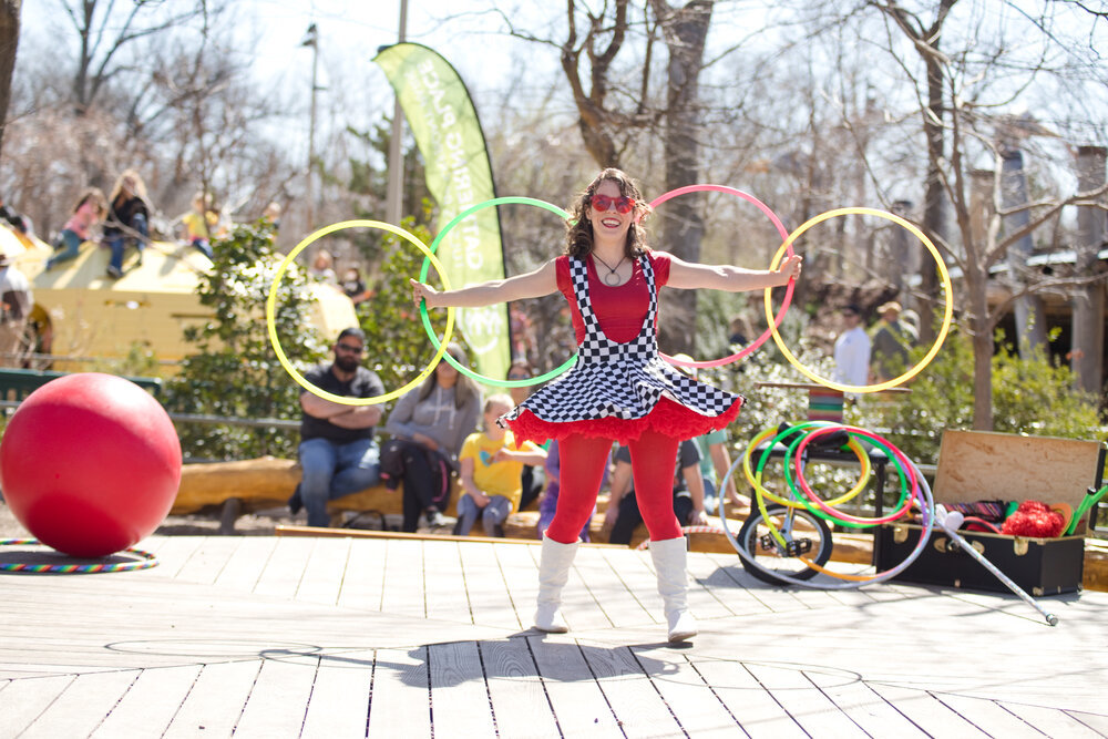 A figure poses with plastic hula hoops