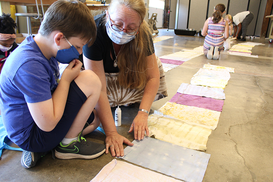 Two figures crouch on the floor to examine dyed cloth.