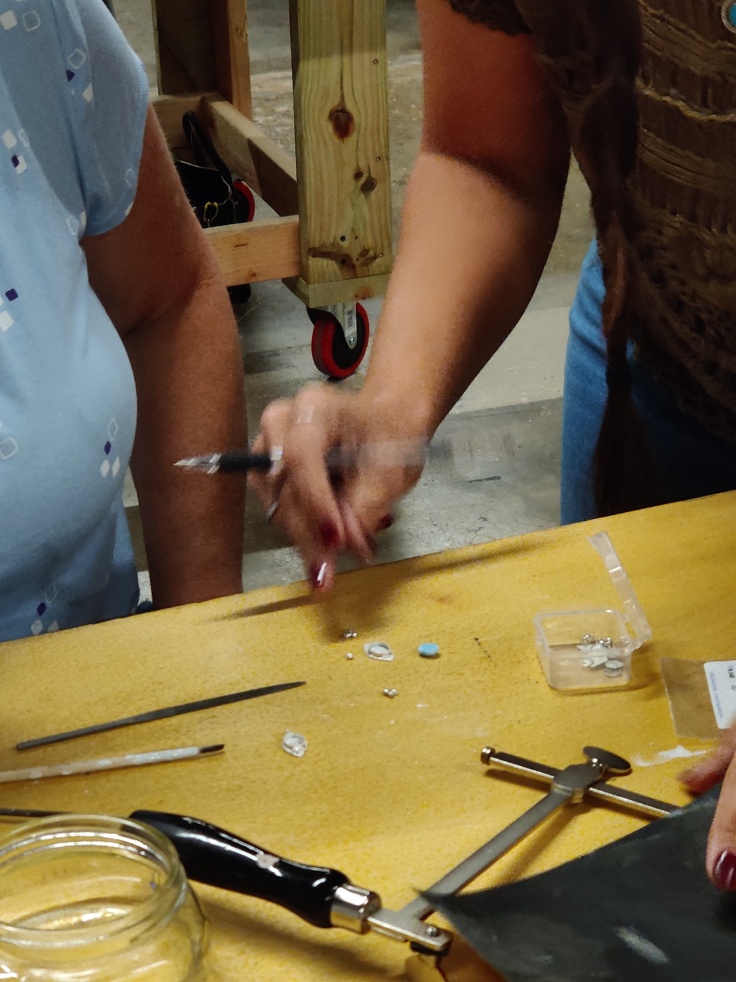 An instructor teaches jewelry making