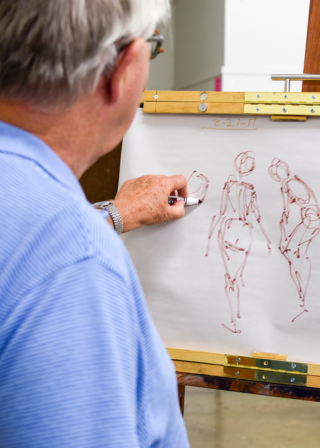 A person draws figures on an easel.