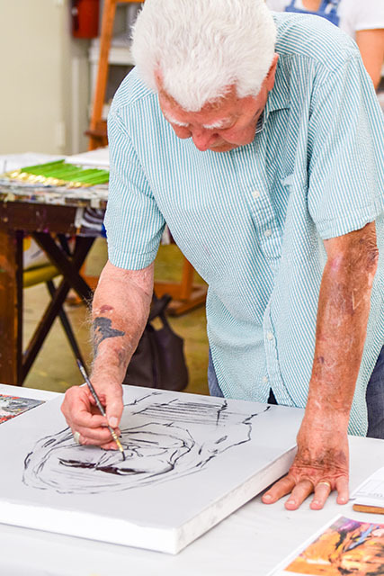 A person with white hair and a tattoo on the right arm paints a figure on canvas