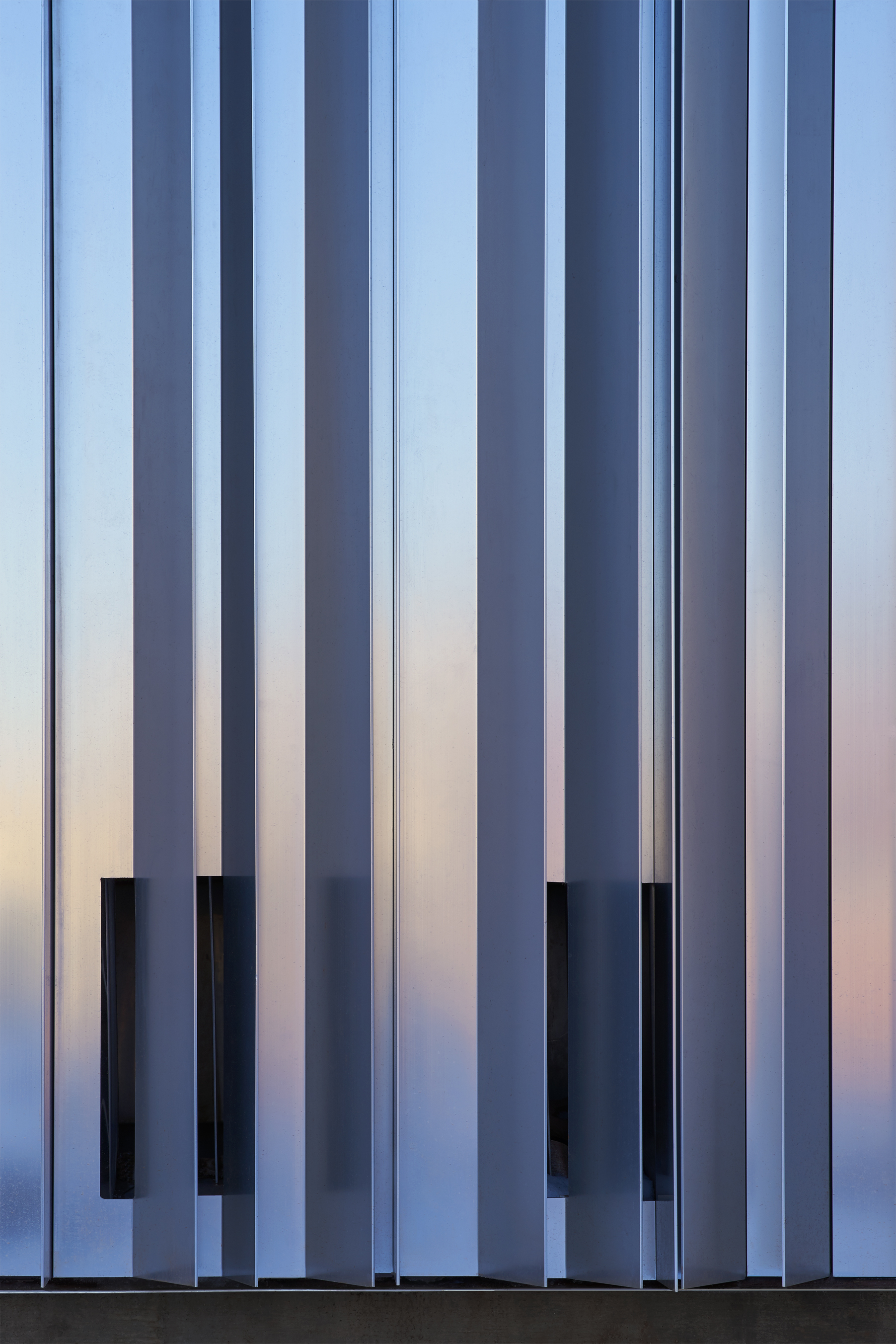 Detail shot of aluminum strips reflecting the pink and purple colors of a sunset