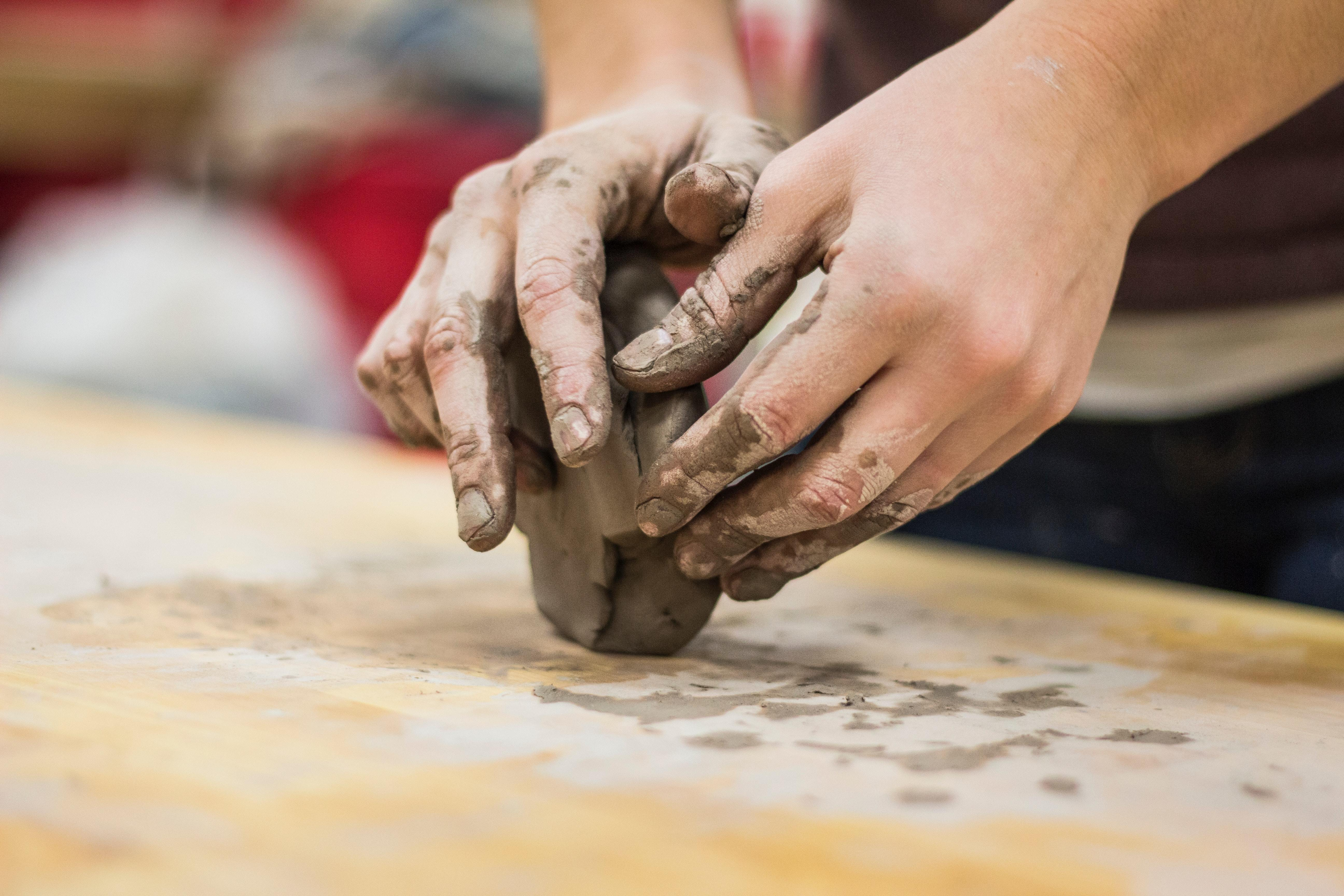 A pair of hands work with a lump of clay on a wooden surface