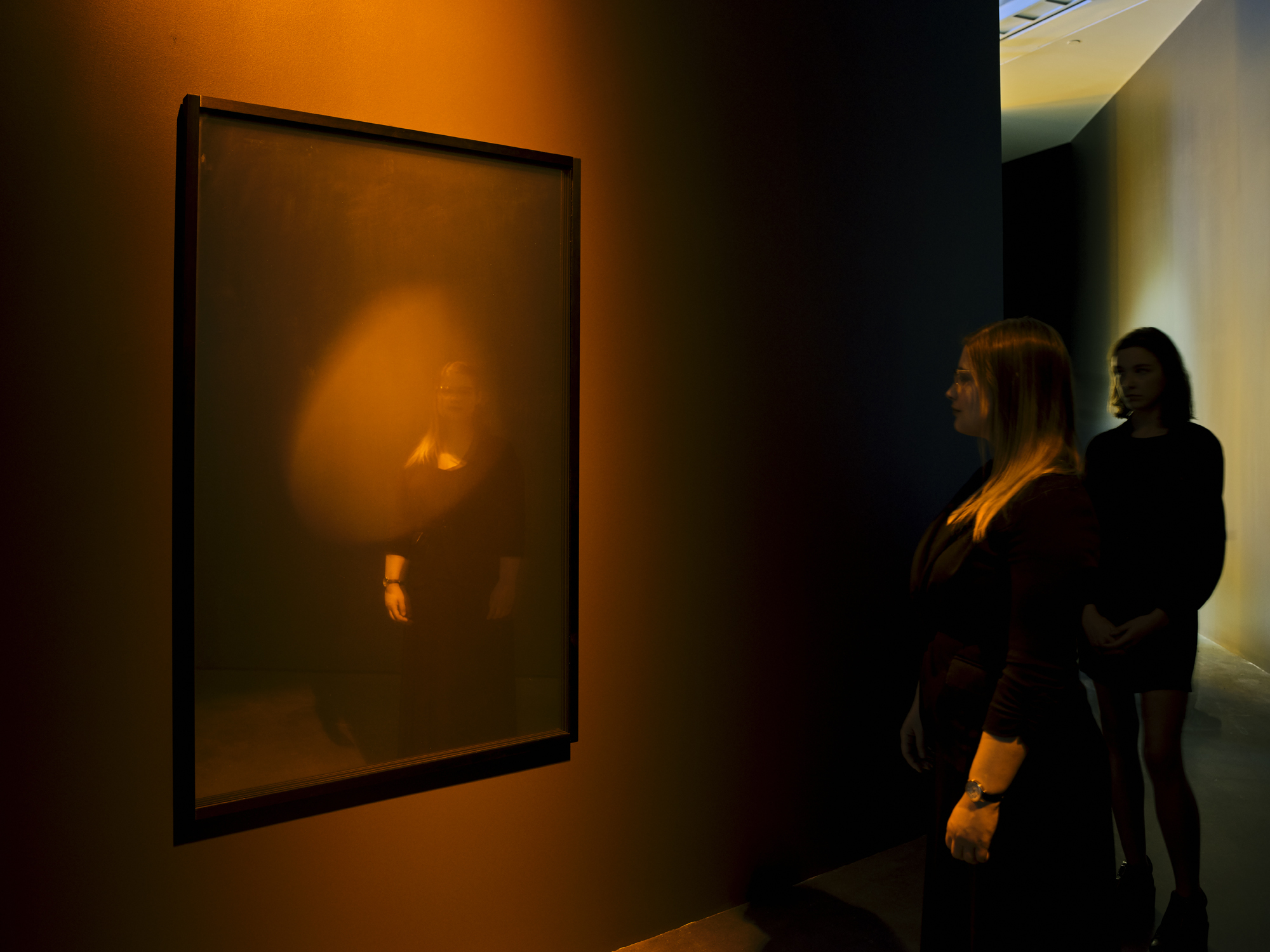 Two figures observe an orange holographic disc on display in a darkened art museum