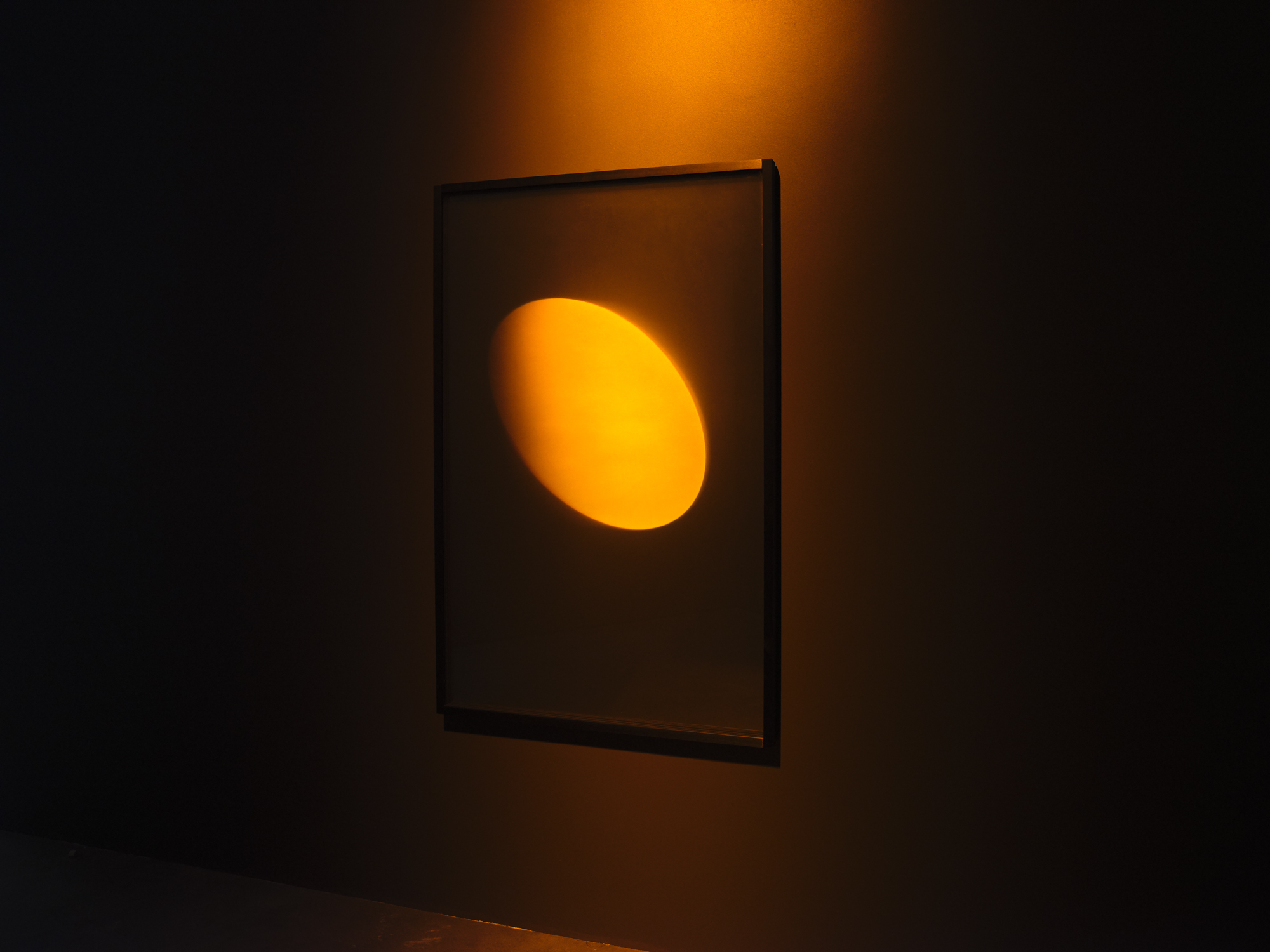 A photo depicts an orange holographic disc on display in a darkened art museum