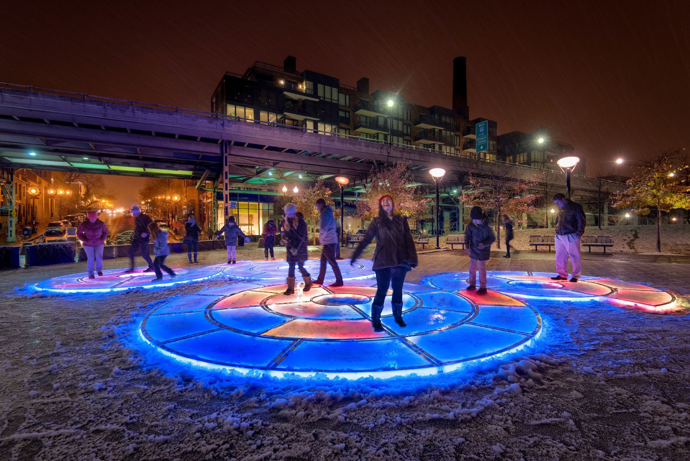 Figures interact with a spiraling, illuminated light sculpture with a nighttime cityscape behind them