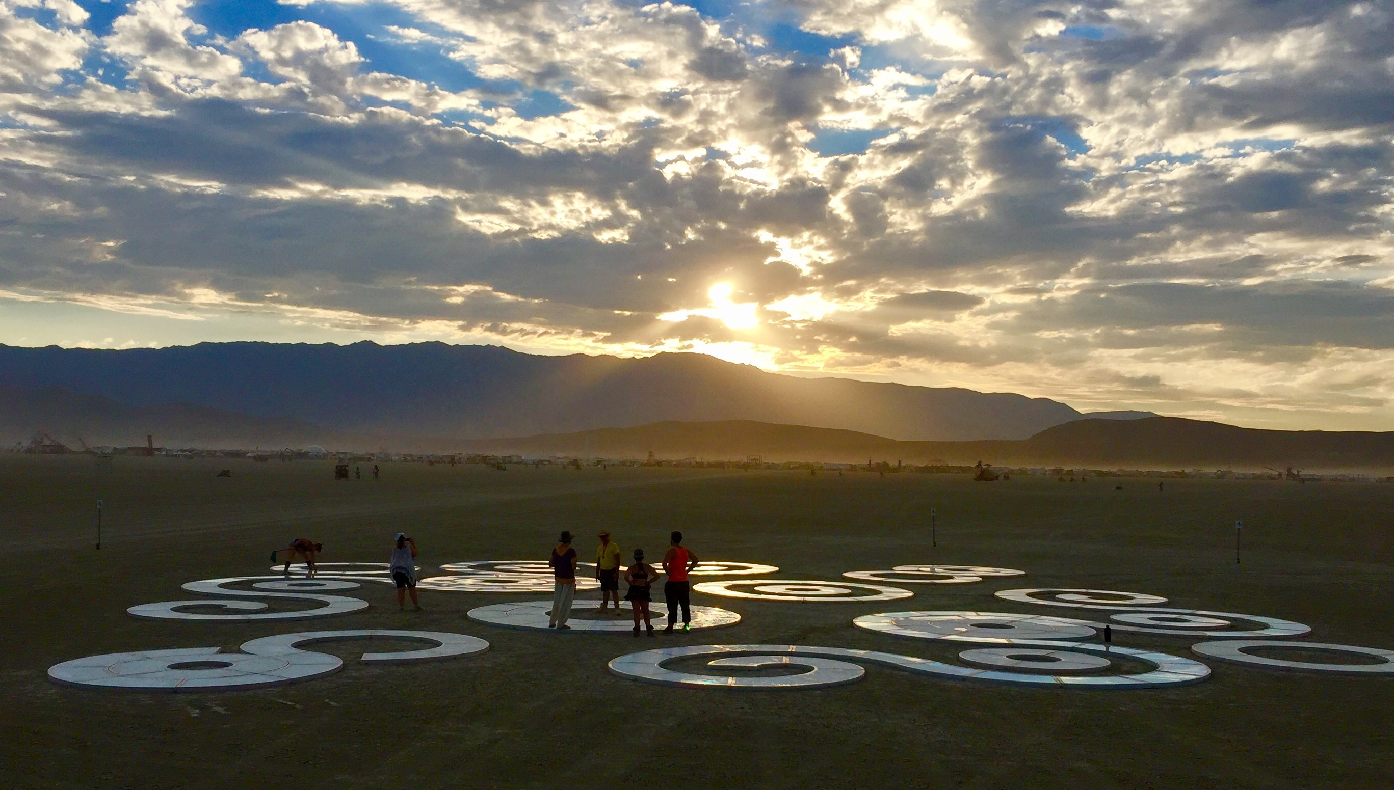 Figures in the distance interact with a spiraling light sculpture in the desert