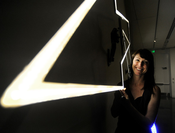 A smiling figure poses with an abstract light sculpture
