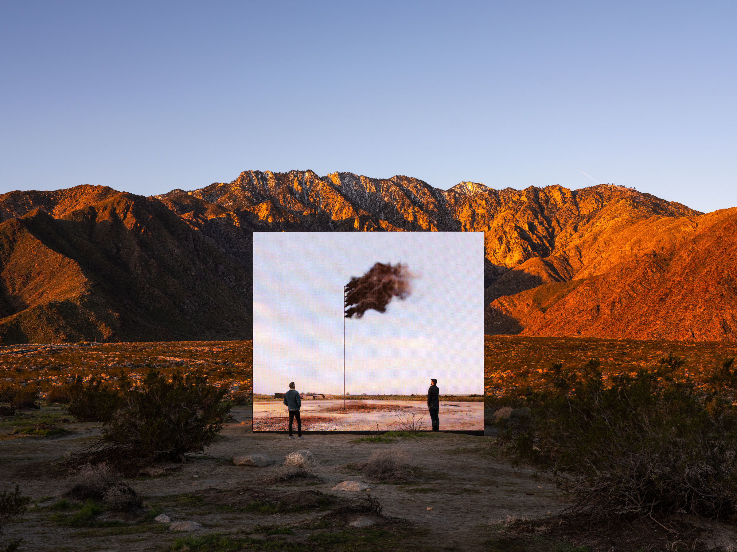 Two figures stand in front of a digital simulation depicting a flag made of smog within a mountainous desert landscape