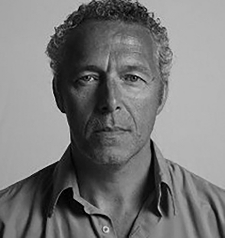 A man stares into the camera without smiling in a tightly cropped black-and-white image