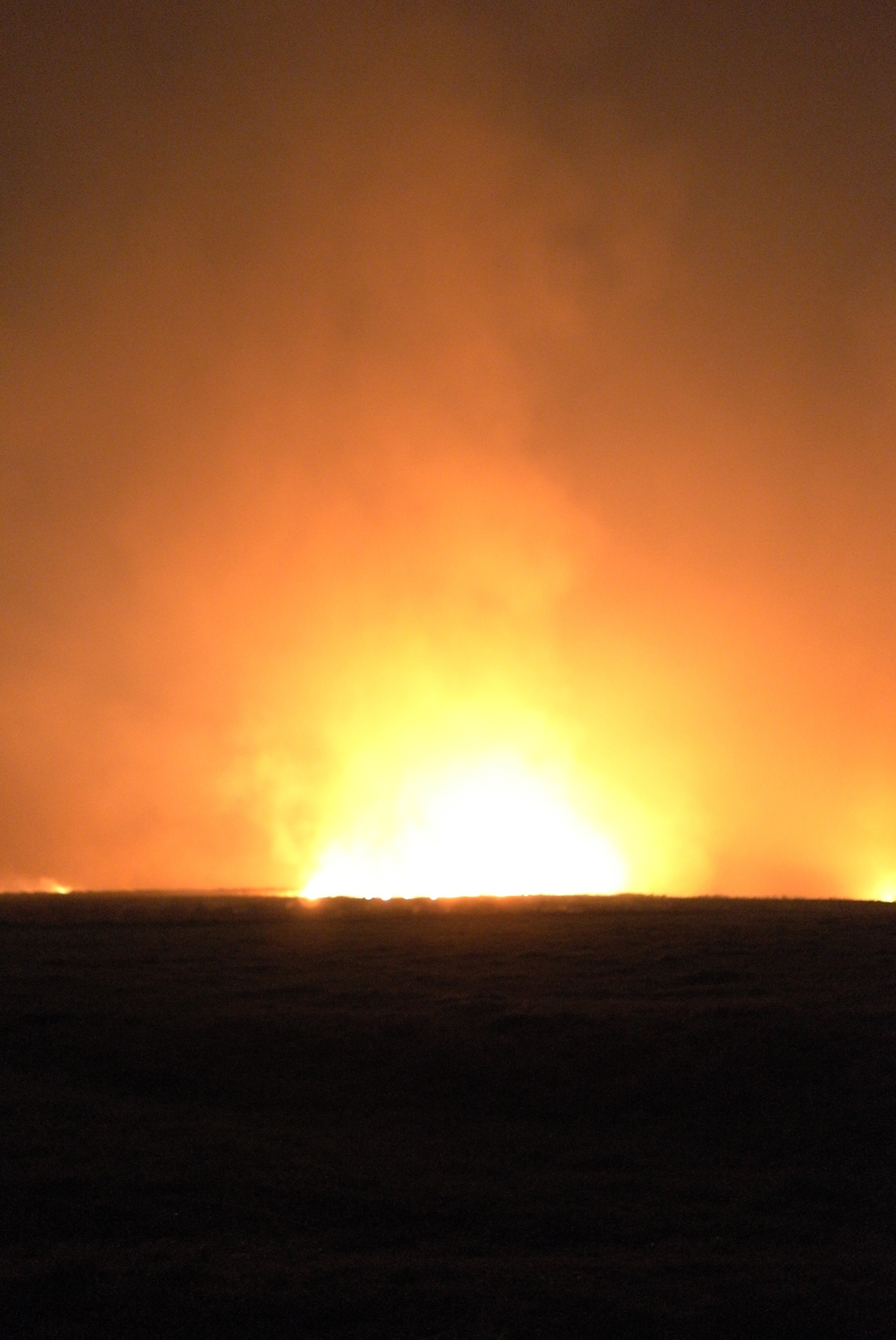 A nighttime image of a large fire burning on the horizon of a dark prairie