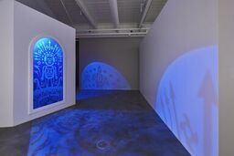 An art installation featuring a human figure and various shapes casts blue light across an empty gallery space
