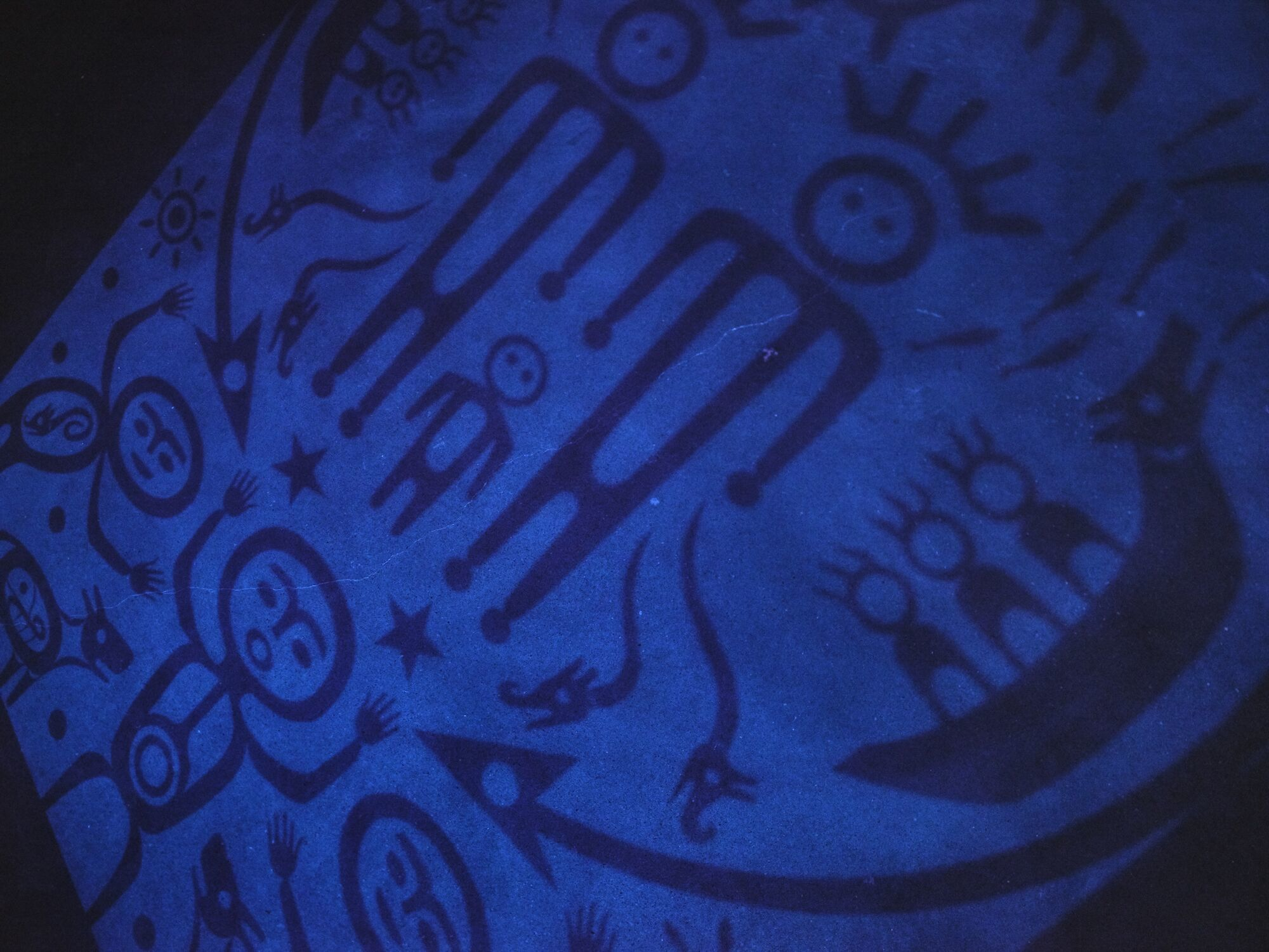 Pictographic figures rendered in blue light