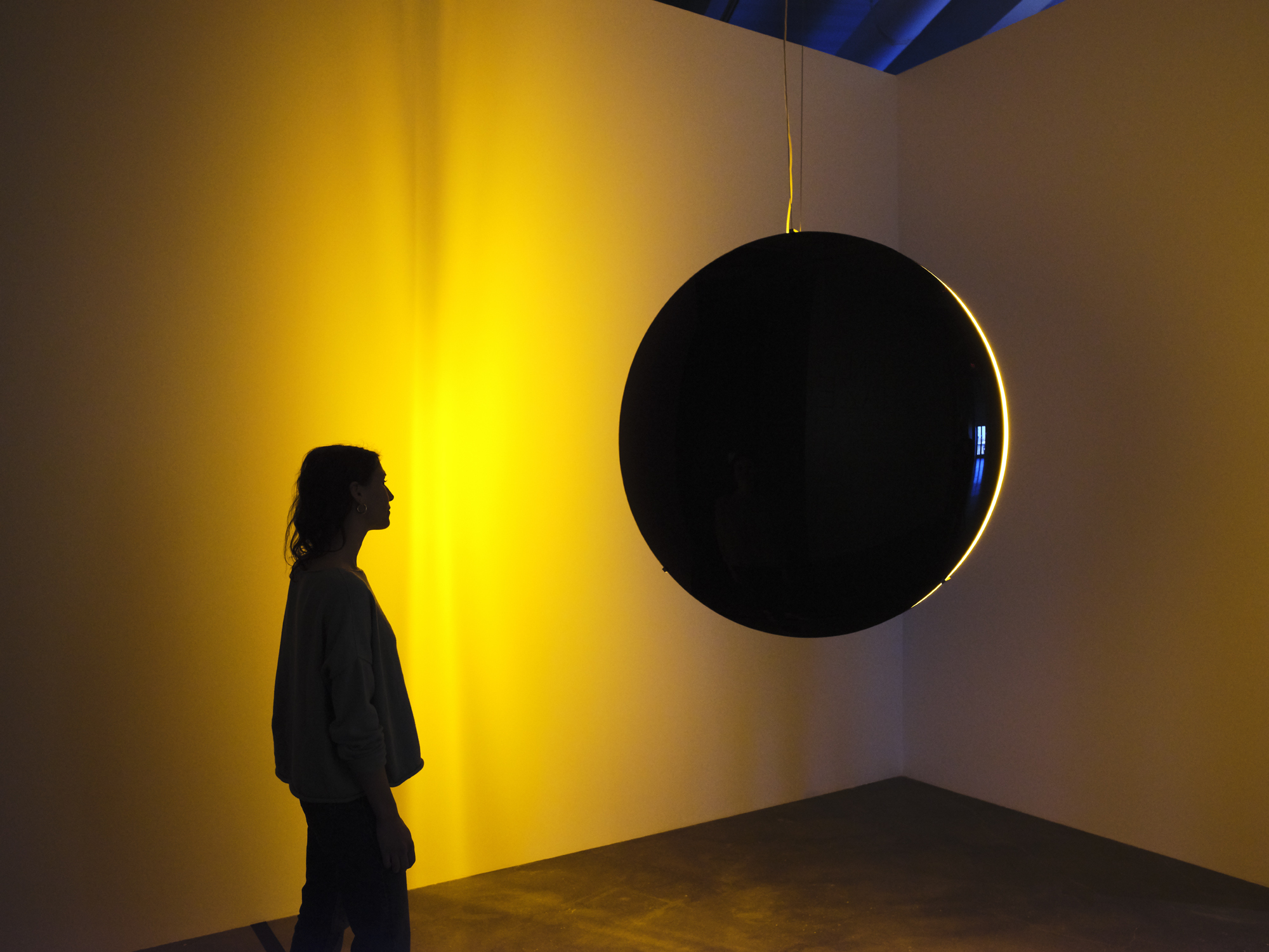 A figure is obscured by shadow as they observe a light sculpture emitting a warm golden glow from a black spherical object