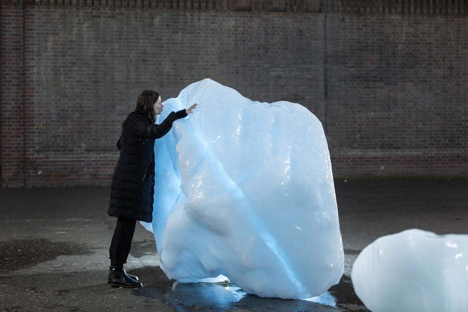 A person kisses a giant block of glacial ice on the streets of London