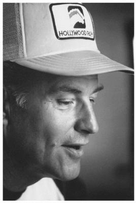 A black and white image of a person wearing a baseball cap
