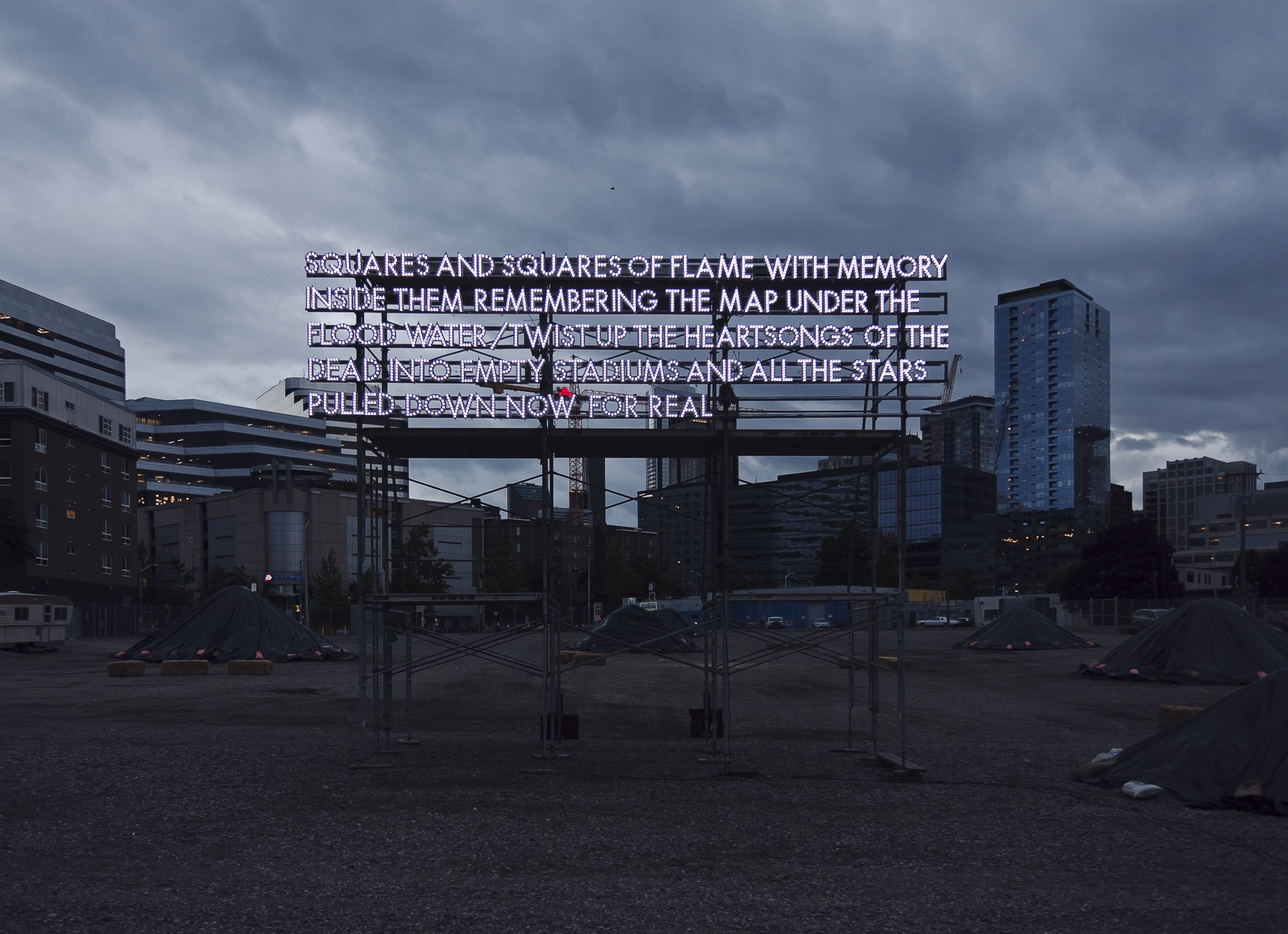 A photograph depicts a work of installation art featuring an illuminated stanza of poetry against a cityscape at dusk
