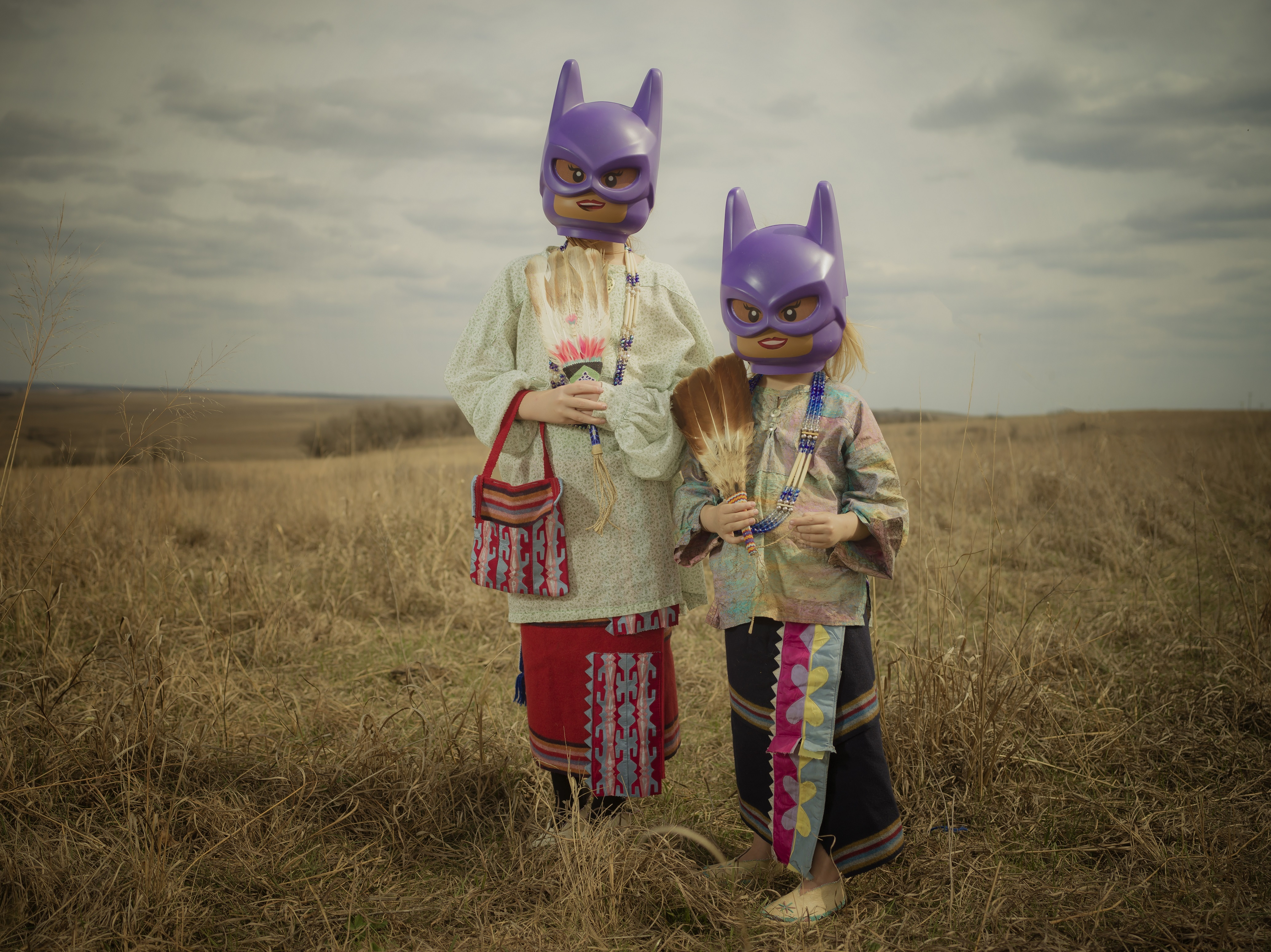 Two children wearing tribal regalia stand in the middle of a prairie wearing Lego Batgirl helmets