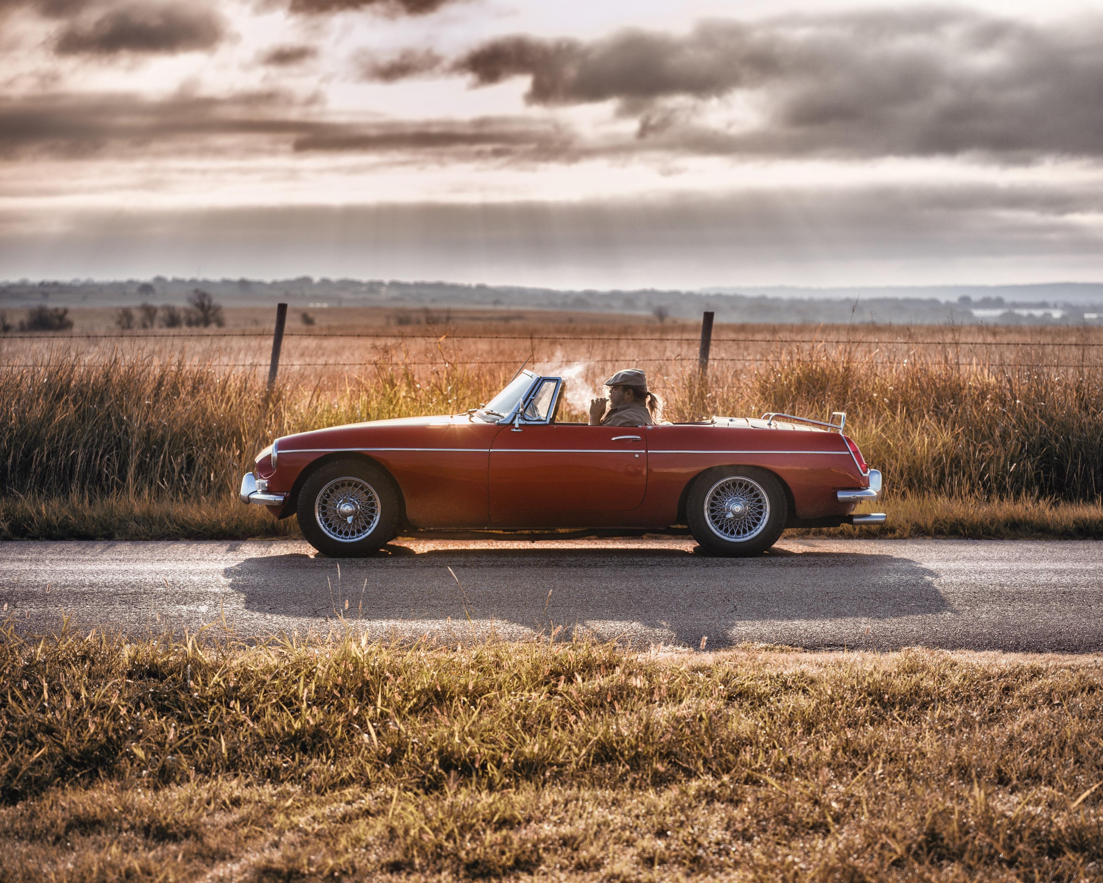 A man smoking a cigar drives down a rural road through a prairie landscape in a classic red car