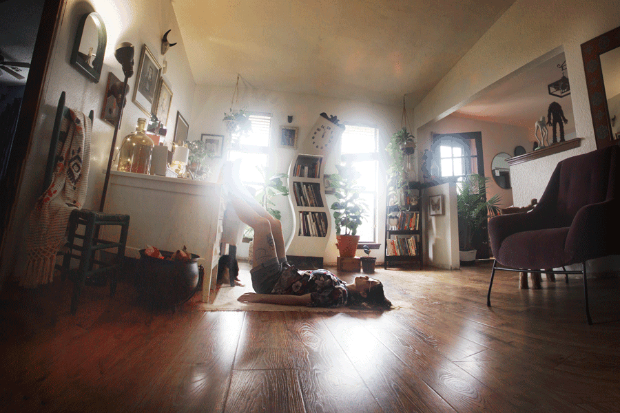 A person lies with their back on the floor in a surreal living room environment