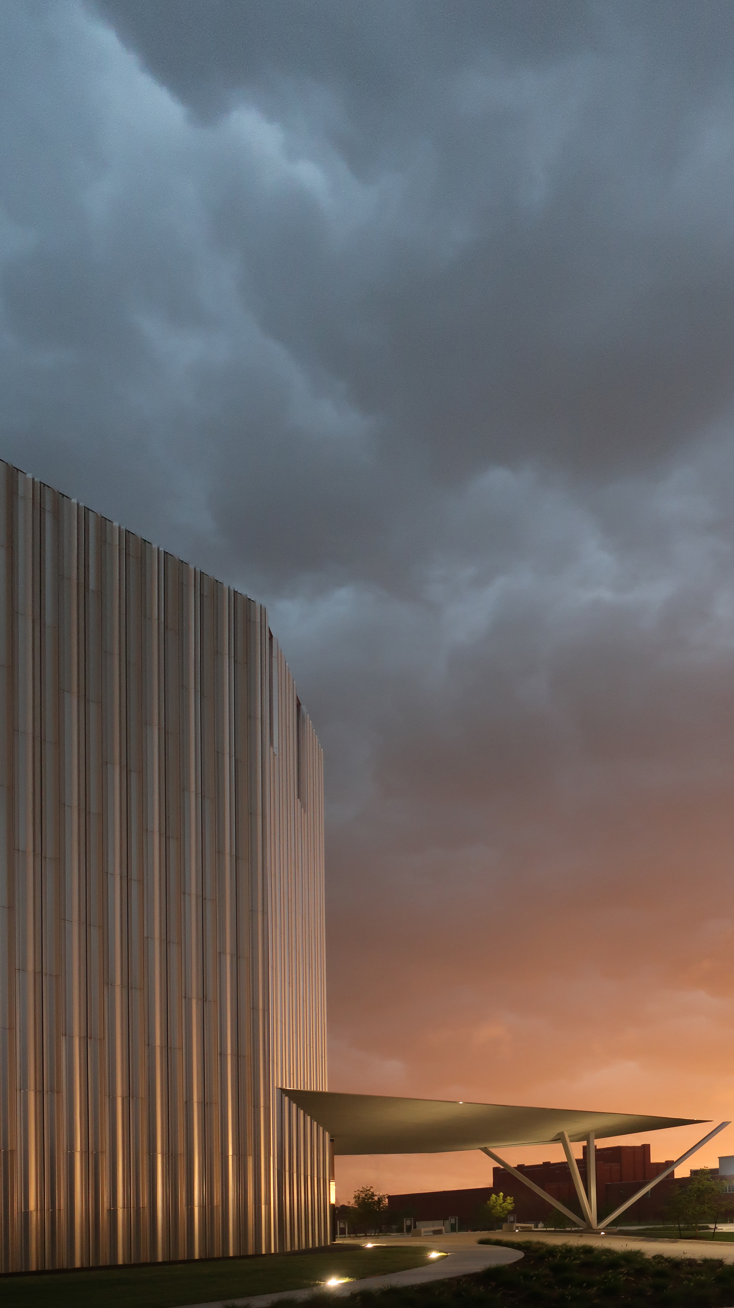 Dark clouds hang over a metal building with a metal awning