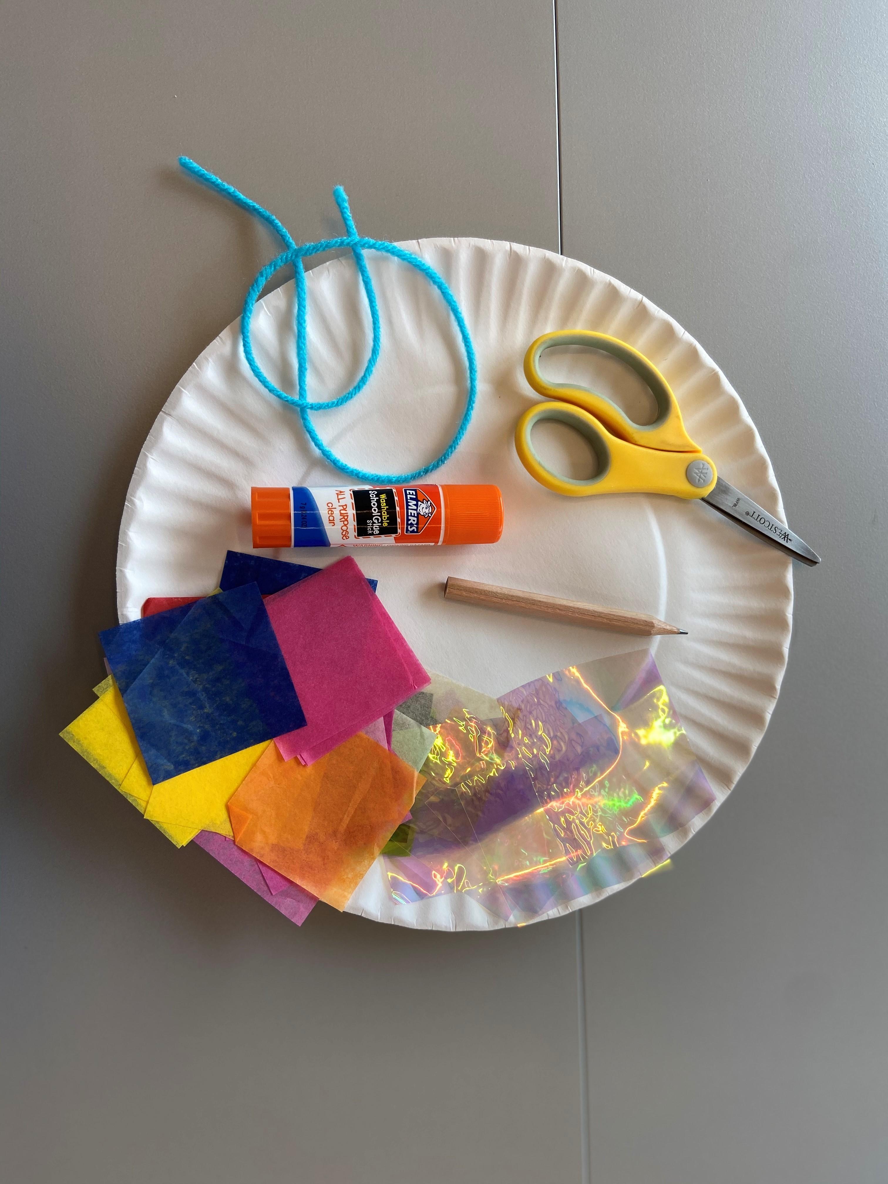 A photo of art supplies on a paper plate: scissors, yarn, glue stick, pencil, etc.