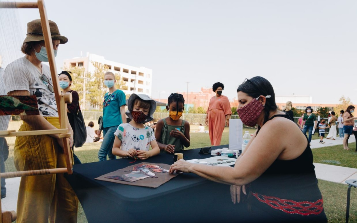 A masked figure demonstrates beadwork for children and families in an outdoor setting