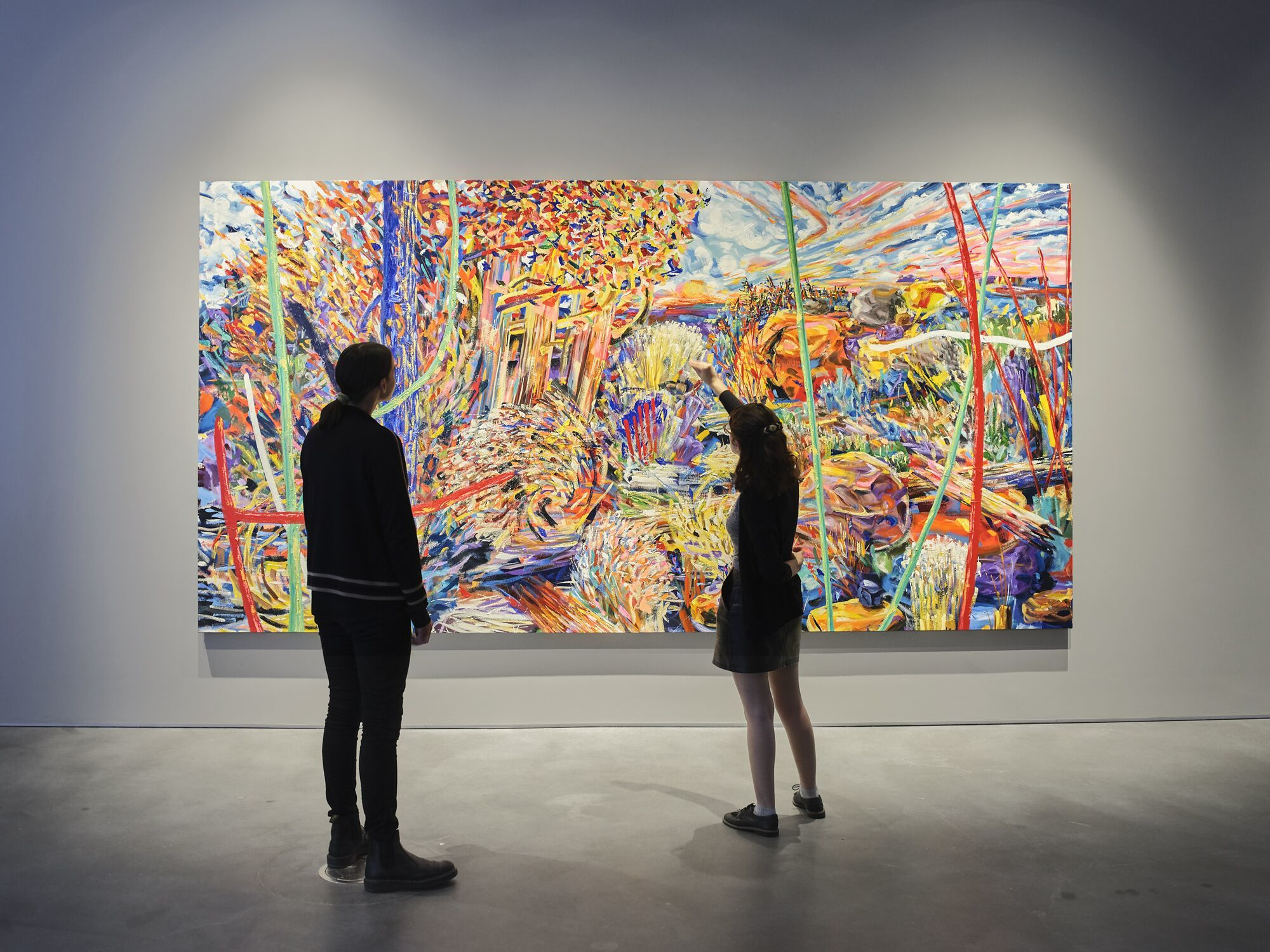Two figures stand in front of a large, colorful and abstract landscape painting