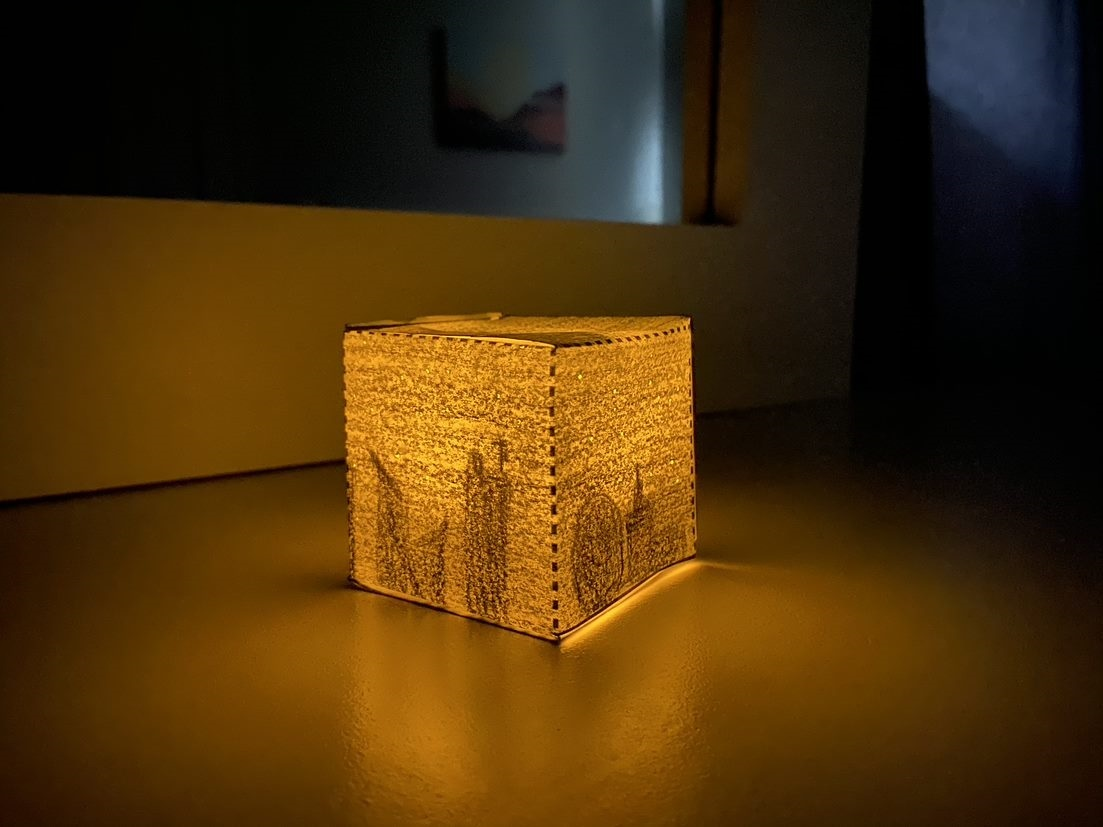 A small, square, paper sculpture sits on the floor illuminating a dim corner