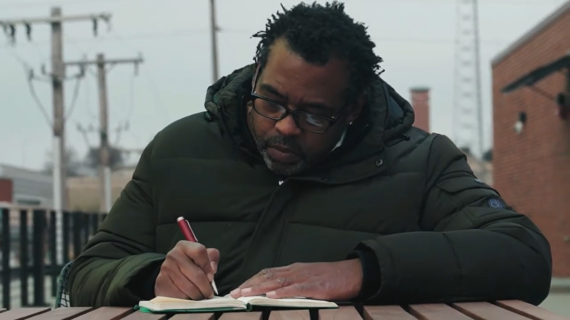 A person in a winter coat and glasses writes in a notebook while sitting at a table outdoors