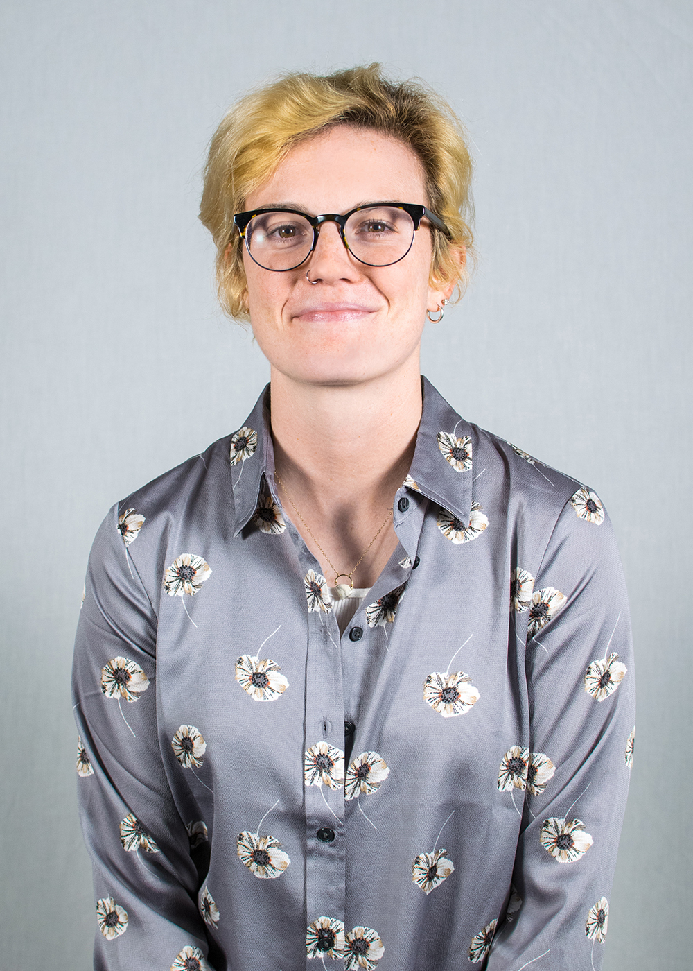 Smiling person with short blonde hair and glasses poses in a floral print shirt