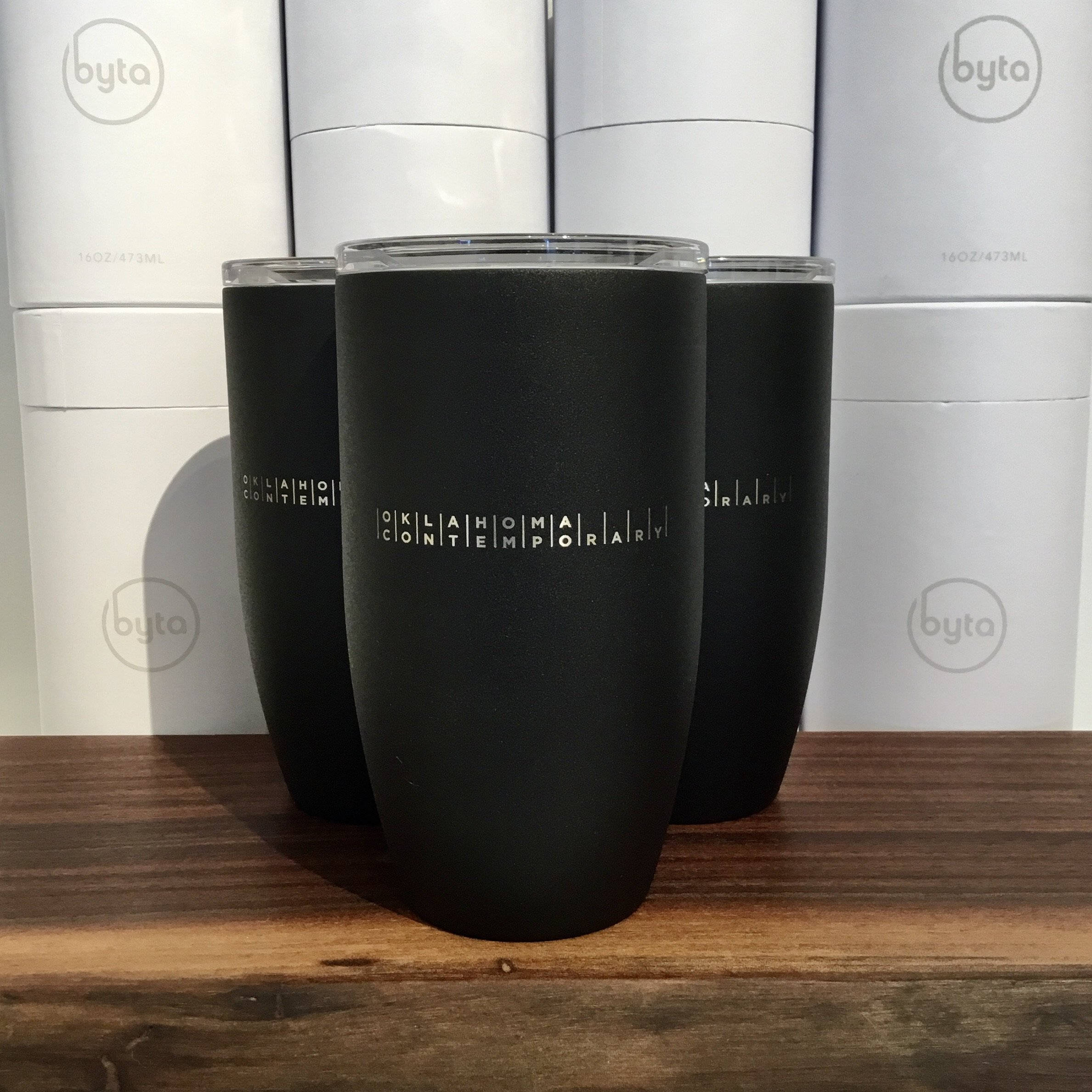 "An image of black tumbler thermoses emblazoned with the words ""Oklahoma Contemporary"""