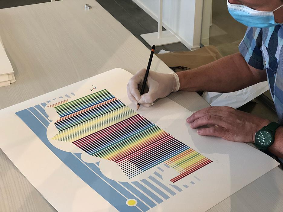 An image of a masked artist signing an art print