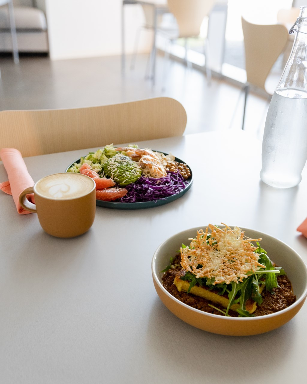 Two meals and a latte served on a white table