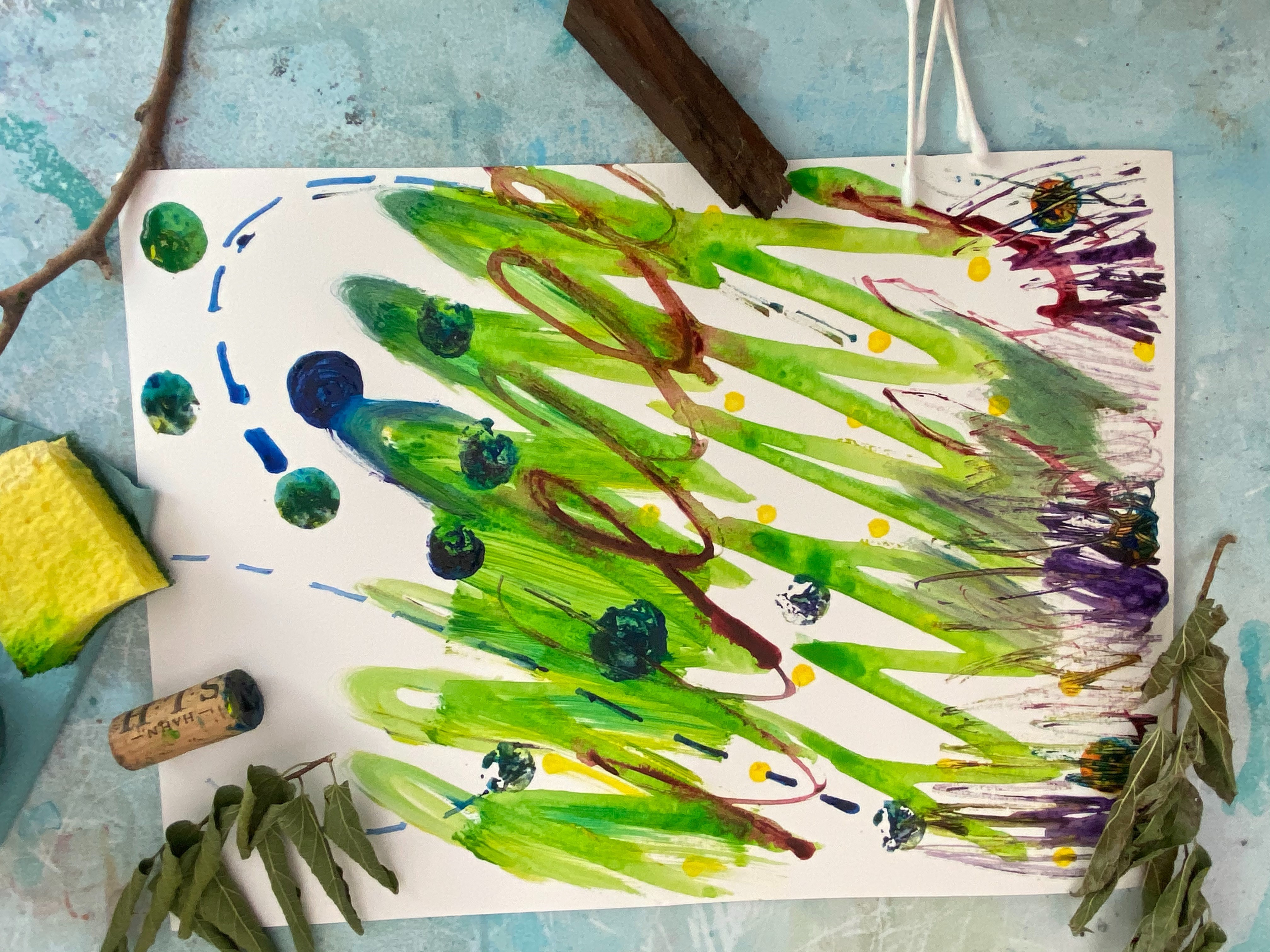 An abstract painting featuring blue, green, purple and yellow -- along with improvised art materials like a sponge, wine cork and leaves