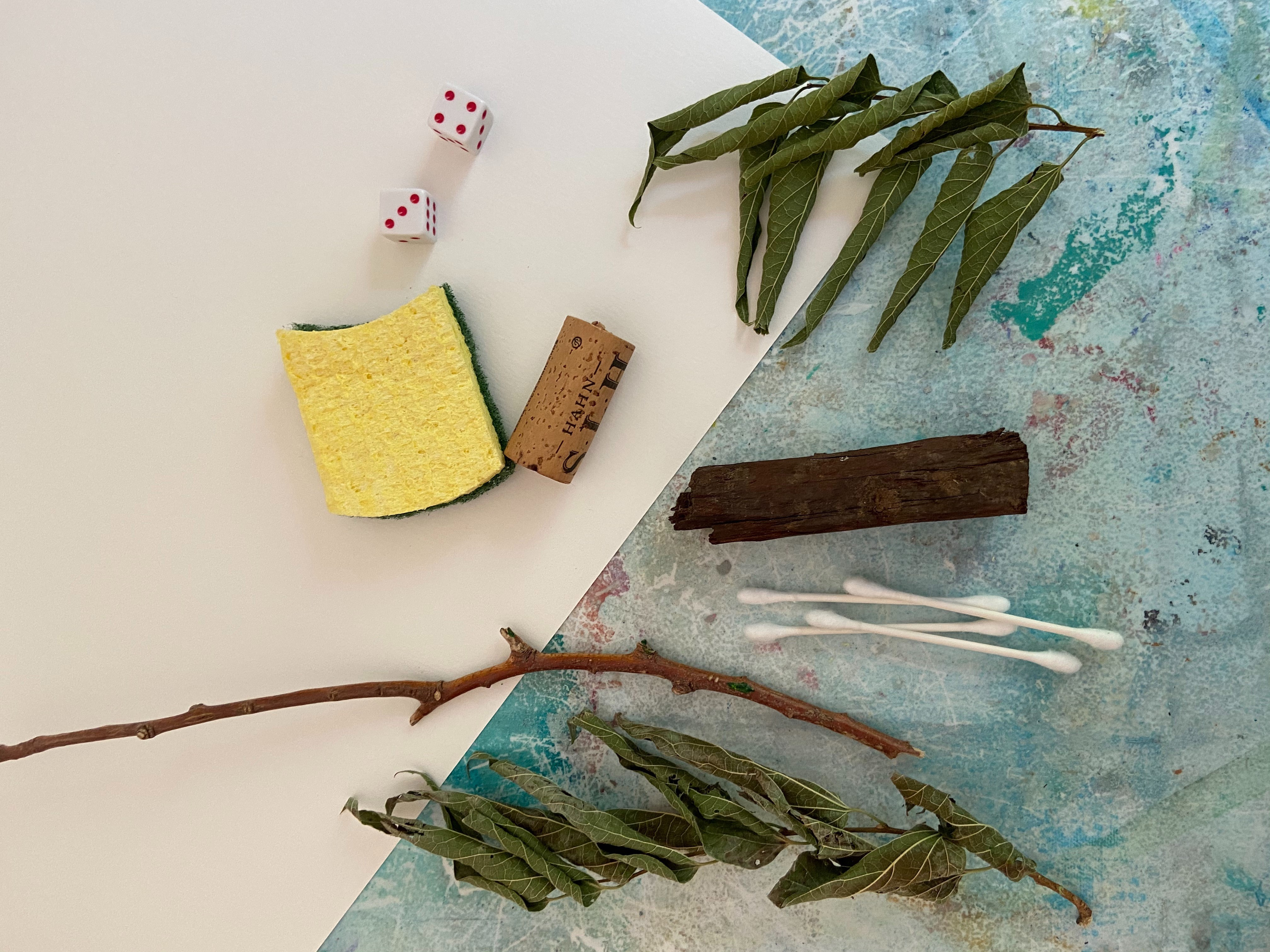 Household art supplies, including Q-tips, a sponge, a wine cork, a pair of dice, leaves and a twig