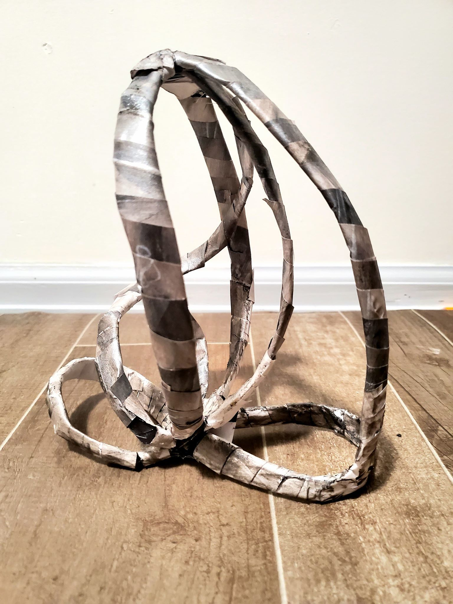 An abstract mixed media sculpture features paper coiled into large overlapping circles