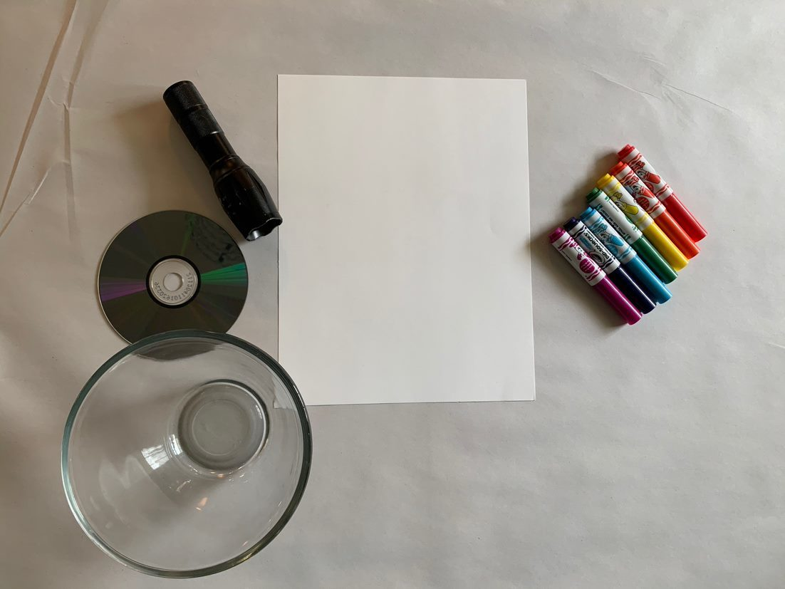 A glass of water, a blank CD, a flashlight, multi-colored markers and a blank piece of paper
