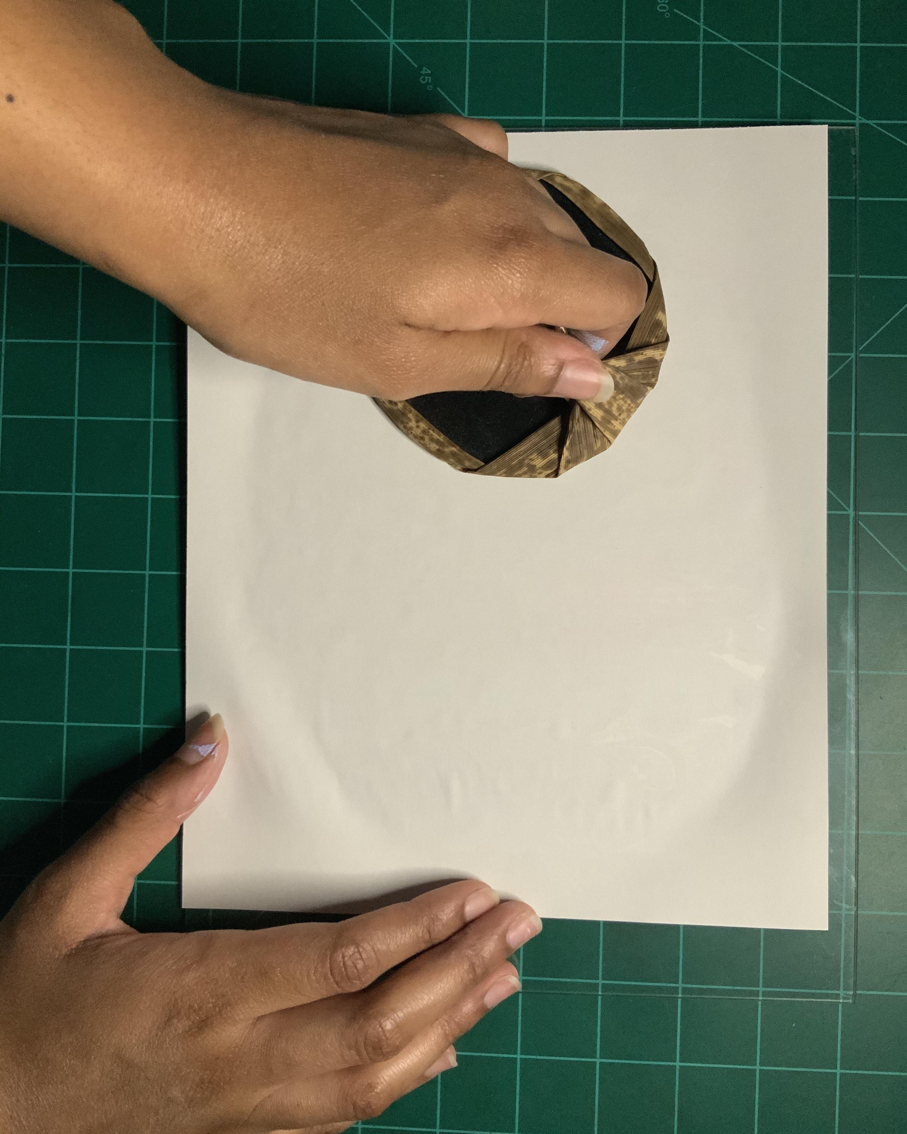 A hand rubs a piece of paper with a baren