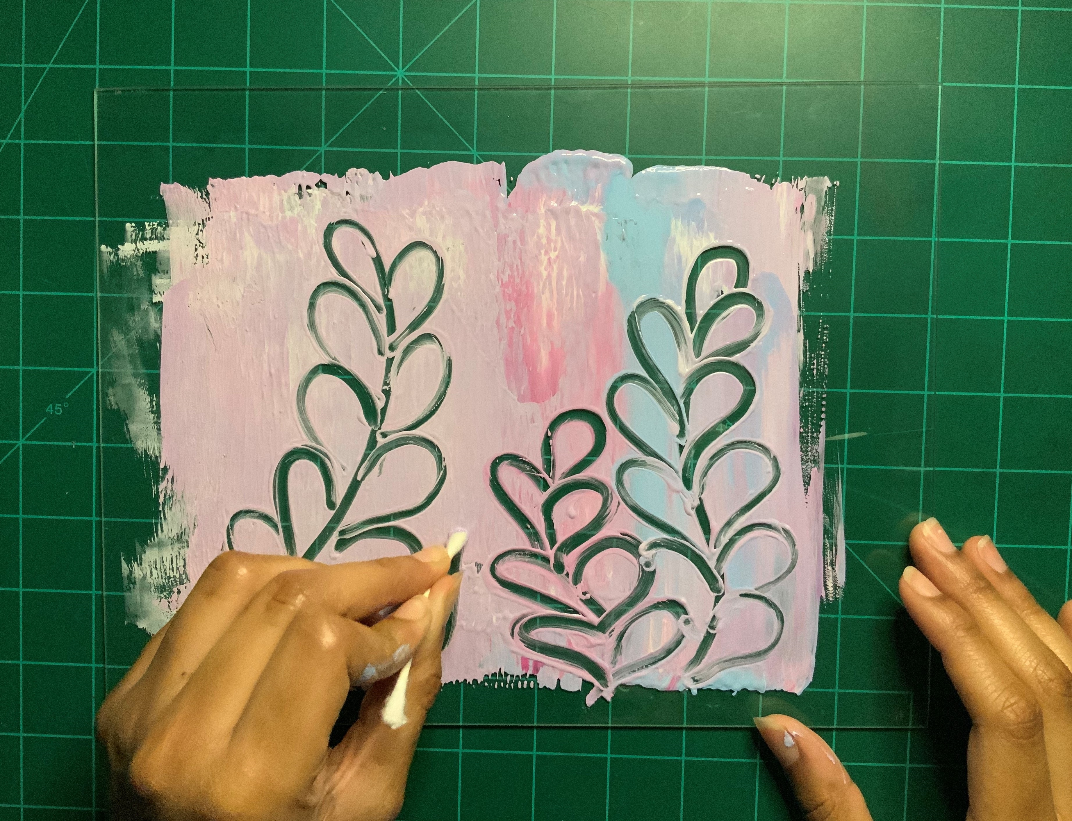 Left hand uses a Q-tip to draw floral shapes in pastel pink and blue paint