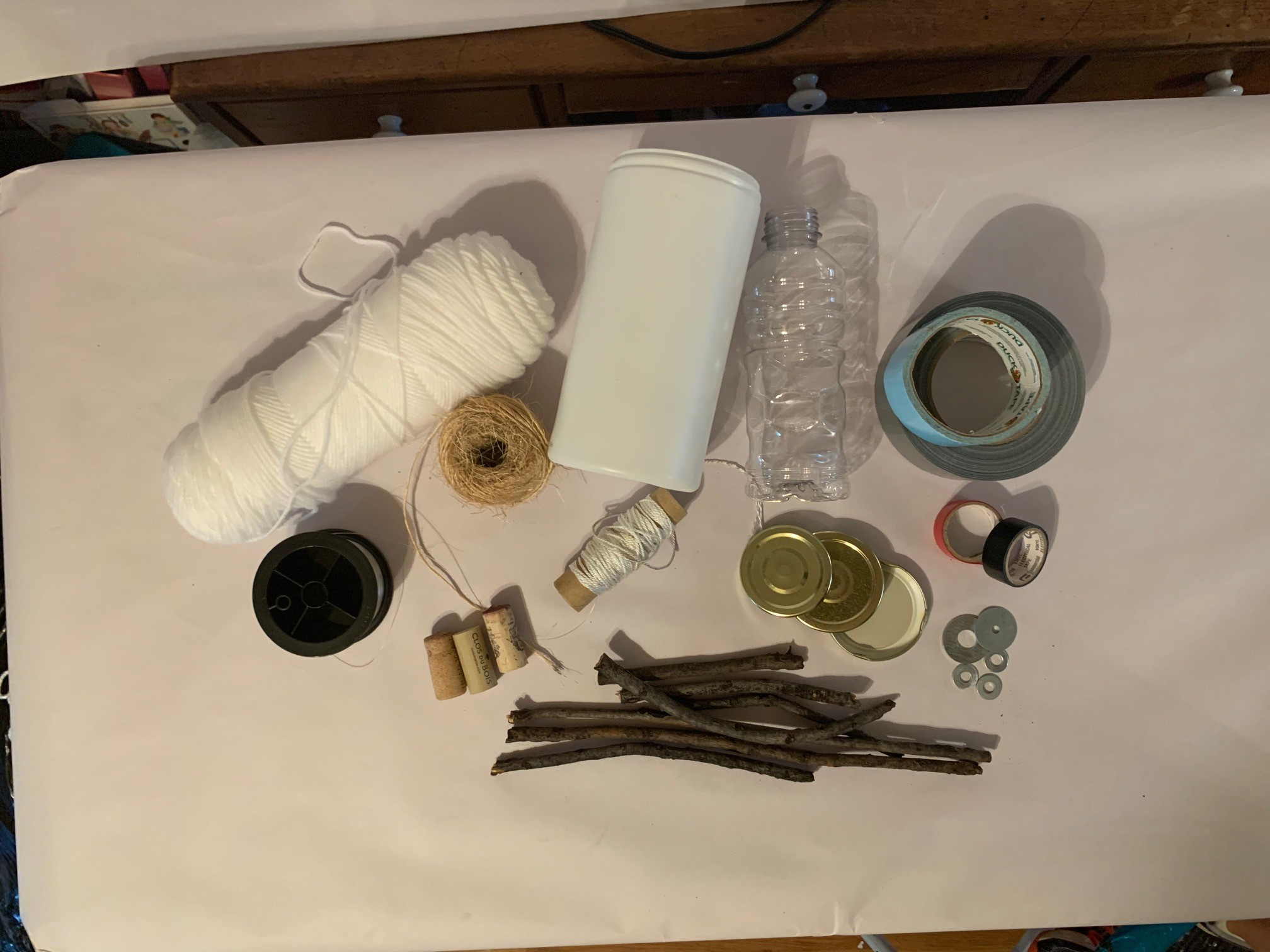 A display of craft items and found materials, including string, sticks, corks, twine and more
