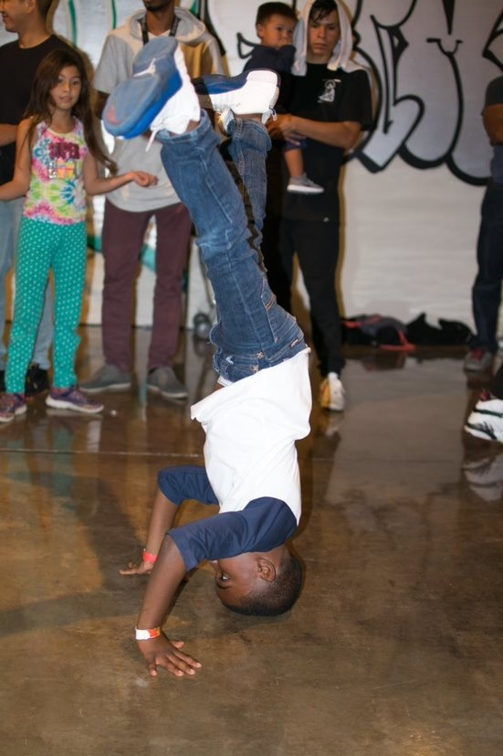 A young boy performs a headstand while dancing as a crowd watches