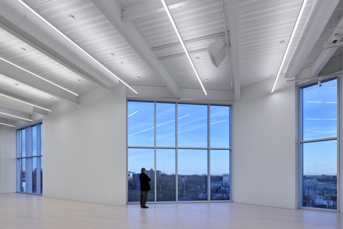 A man stands in an empty studio with wooden floors and large windows