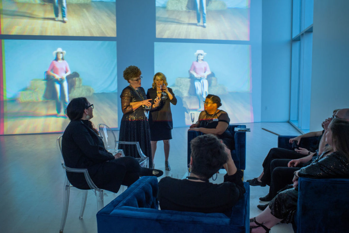 People stand and sit in a group in a room with images on a large screen