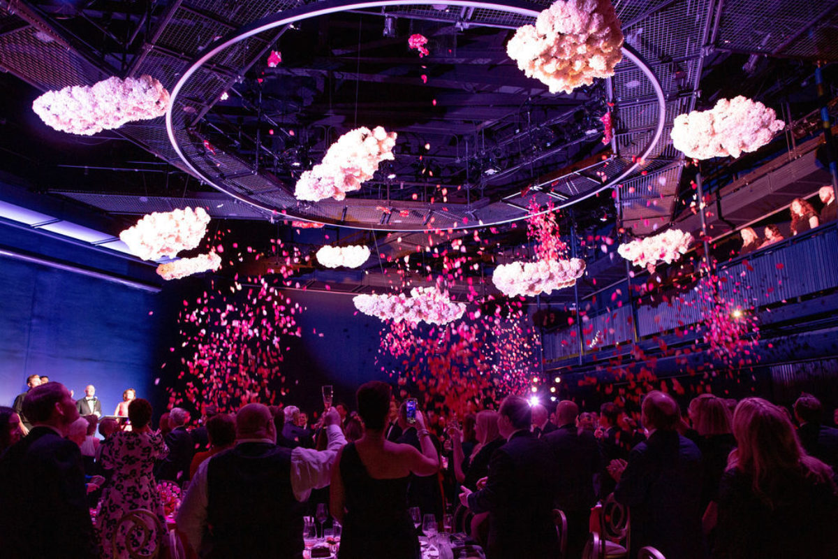Flowers fall from the ceiling on a room full of people dressed in black tie attire
