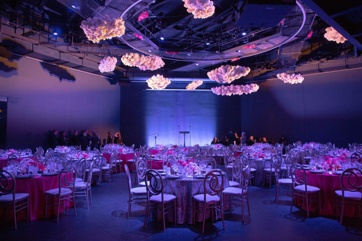 A large barely lit room filled with tables and chairs , decorated with flowers with flower sculptures hanging from the ceilng